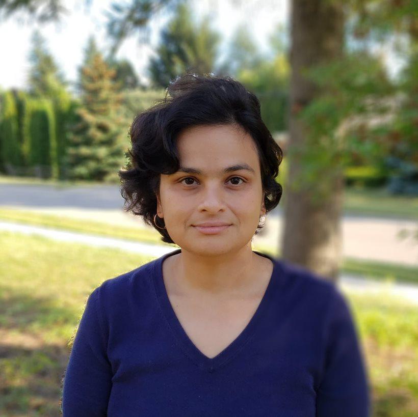 Photo of Dr. Ashirbani Saha wearing a dark blue shirt with tress behind her